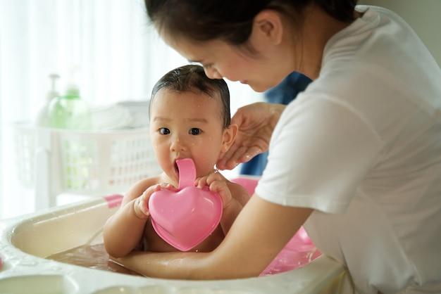 Asiatische schöne mutter, die kleines nettes baby hält und ein bad ihr kind sitzt in der badewanne im raum nimmt Premium Fotos