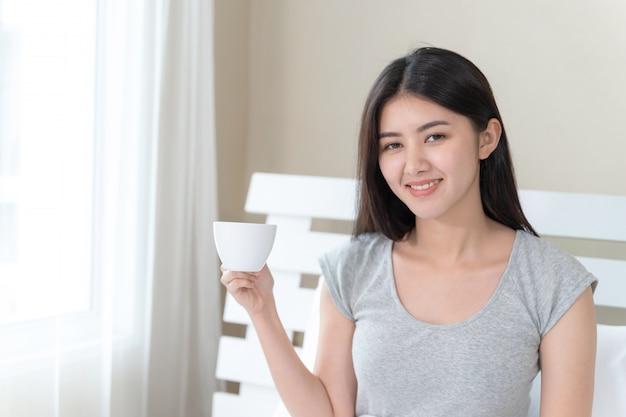 Asiatische schönheit, die auf bett im schlafzimmer sitzt und in der hand kaffeetasse mit glücklichem hält Kostenlose Fotos