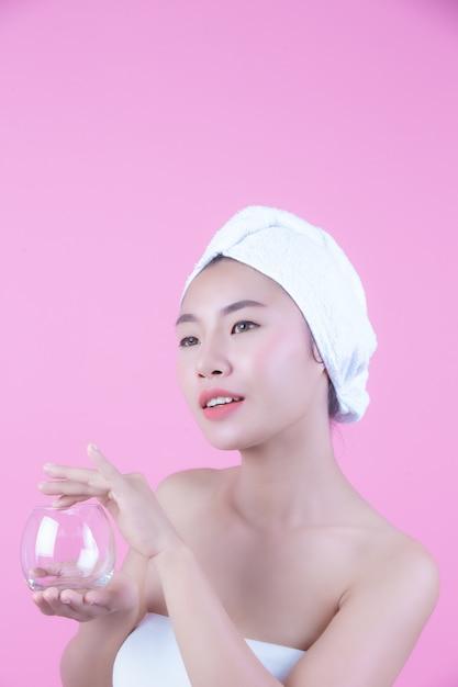 Asiatische schönheit, die das gesicht auf einem rosa hintergrund, einer kosmetologie und einem badekurort abwischt. Kostenlose Fotos