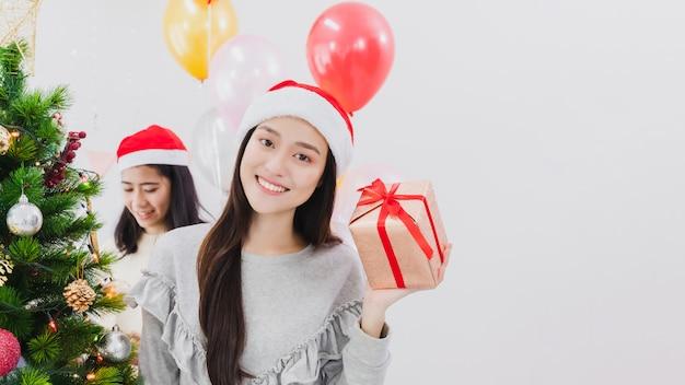Asiatische schönheit verziert weihnachtsbaum im reinraum mit der hand, die geschenkbox hält lächelndes gesicht und glücklich, festivel neujahrsfeiertag zu feiern. Premium Fotos