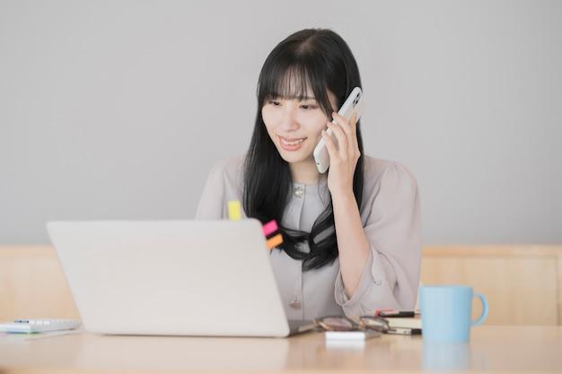 Asiatische schwarzhaarige frau, die von zu hause aus mit einem laptop arbeitet Premium Fotos
