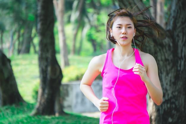 Asiatische sportfrau, die, laufend in park rüttelt Premium Fotos