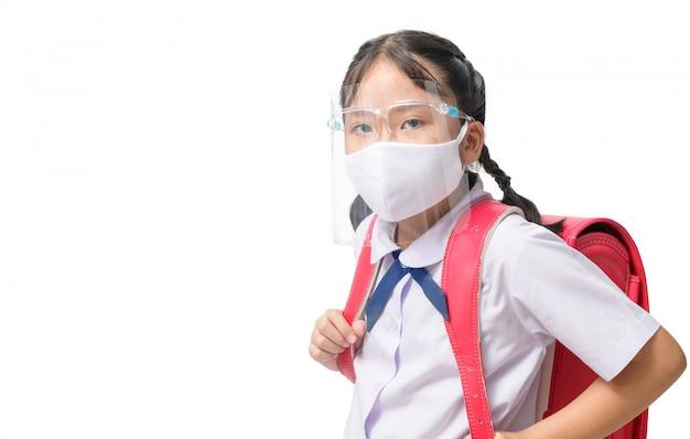 Asiatische studentin trägt gesichtsschutz und maske trägt schultasche isoliert Premium Fotos