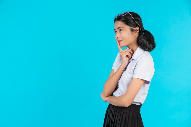 Asiatische studentinnen, die in den verschiedenen positionen auf einem blau aufwerfen. Kostenlose Fotos