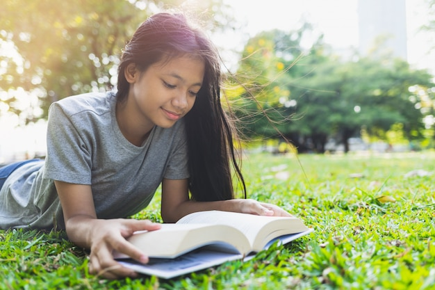 Asiatische teenager lügen lesen bücher auf dem rasen im park Premium Fotos