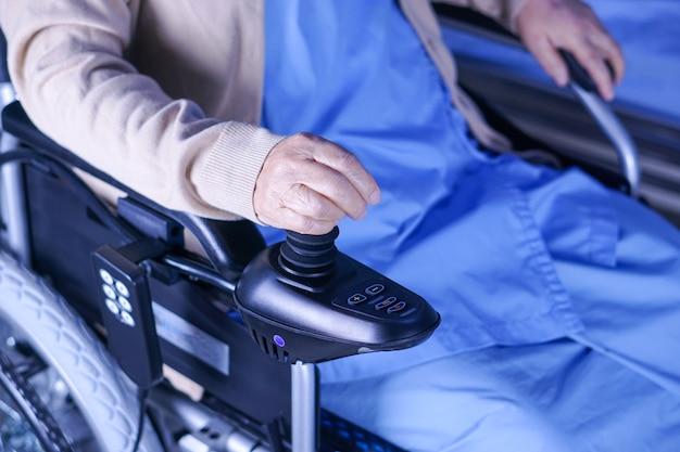 Asiatischer älterer damenfrauenpatient auf elektrischem rollstuhl am pflegeheim. Premium Fotos