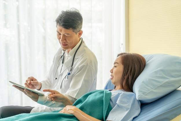 Asiatischer älterer doktor, der auf krankenhausbett sitzt und mit weiblichem patienten sich bespricht Premium Fotos