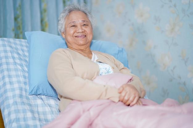 Asiatischer älterer frauenpatient, der auf bett im krankenhaus sitzt Premium Fotos