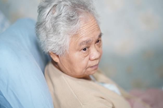 Asiatischer älterer frauenpatient, der auf bett im krankenhaus sitzt. Premium Fotos