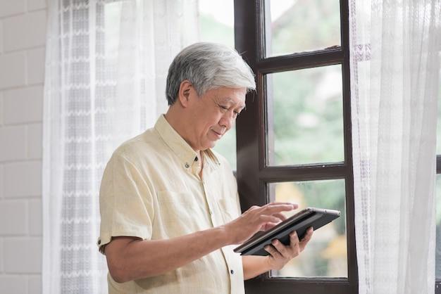 Asiatischer älterer mann, der die tablette zu hause überprüfendes social media nahe fenster im wohnzimmer verwendet. lebensstil ältere männer zu hause konzept. Kostenlose Fotos
