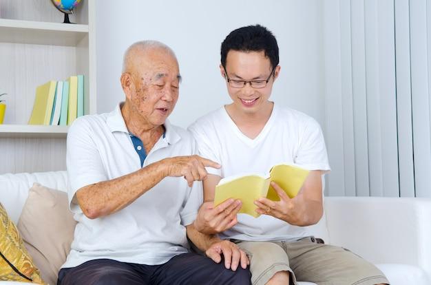 Asiatischer älterer mann, der zu hause ein buch mit seinem sohn liest Premium Fotos