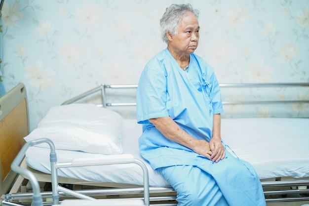 Asiatischer älterer oder älterer frauenpatient alter dame, der auf bett in der krankenstation mit hoffnung sitzt und auf ihren verwandten wartet: gesundes starkes medizinisches konzept. Premium Fotos