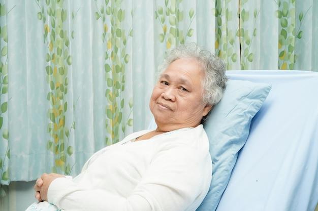 Asiatischer älterer oder älterer frauenpatient alter dame, der auf bett sitzt Premium Fotos
