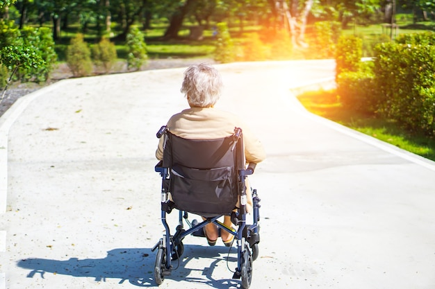 Asiatischer älterer oder älterer frauenpatient der alten dame auf rollstuhl im park. Premium Fotos