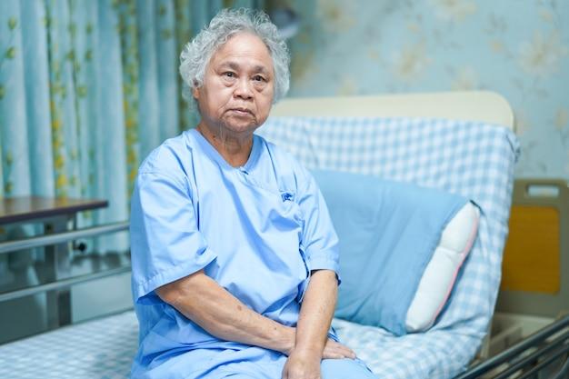 Asiatischer älterer oder älterer frauenpatient der alten dame, der auf bett in krankenpflegekrankenhaus sitzt. Premium Fotos