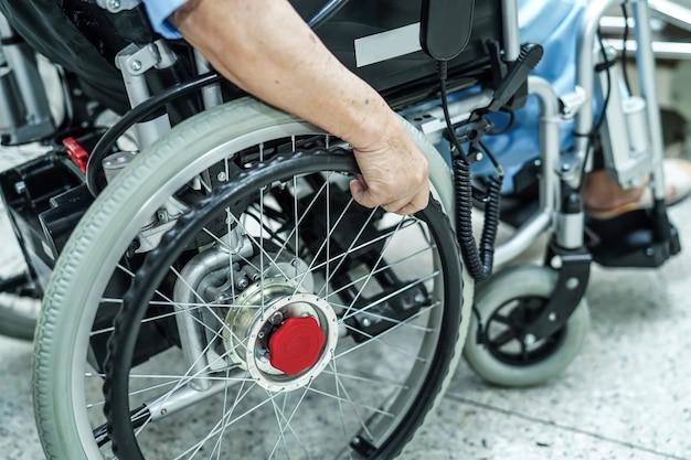 Asiatischer älterer oder älterer fraupfleger der alten dame auf elektrischem rollstuhl am pflegeheim Premium Fotos