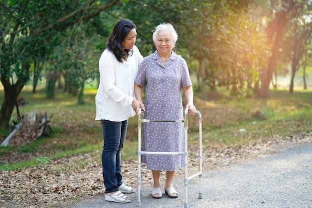 Asiatischer älterer oder älterer geduldiger weg alter dame mit wanderer im park. Premium Fotos