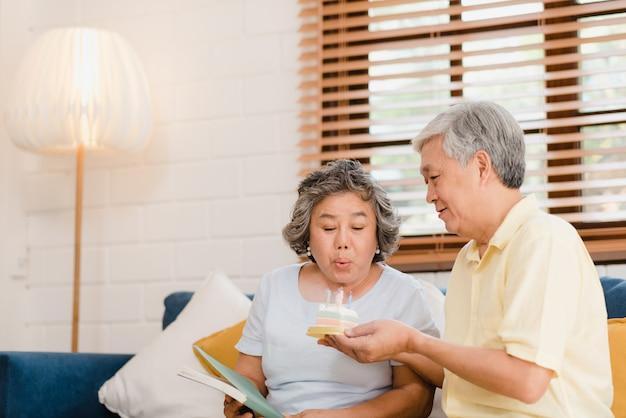 Asiatischer älterer paarmann, der den kuchen hält, der zu hause den geburtstag der frau im wohnzimmer feiert. japanische paare genießen liebesmoment zusammen zu hause. Kostenlose Fotos
