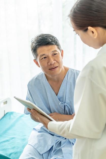 Asiatischer älterer patient auf krankenhausbett besprechend mit ärztin Premium Fotos