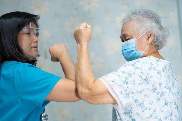 Asiatischer arzt und älterer patient stoßen an die ellbogen, um das covid-19-coronavirus zu vermeiden. Premium Fotos