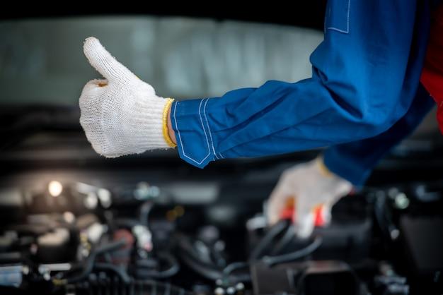 Asiatischer automechaniker in einer autowerkstatt überprüft den motor. für kunden, die autos für reparaturarbeiten verwenden, arbeitet der mechaniker in der garage. Premium Fotos