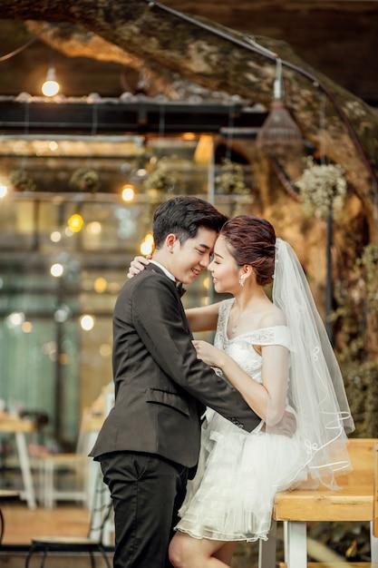 Asiatischer bräutigam und asiatische braut sind nah zusammen und sind im begriff, sich mit einem lächelnden und glücklichen gesicht zu küssen. Premium Fotos