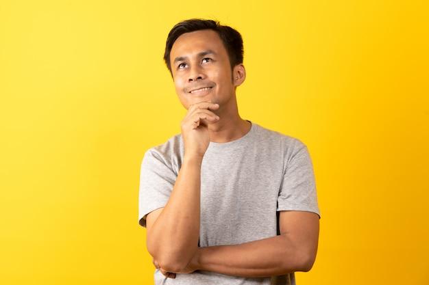 Asiatischer denkender und lächelnder mann Premium Fotos