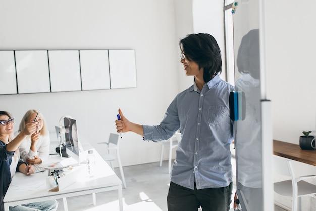 Asiatischer entwickler, der nahe flipchart steht und blonde frau in gläsern betrachtet. innenporträt des brünetten geschäftsmannes, der grafik an der weißen tafel schreibt und kollegen hört. Kostenlose Fotos