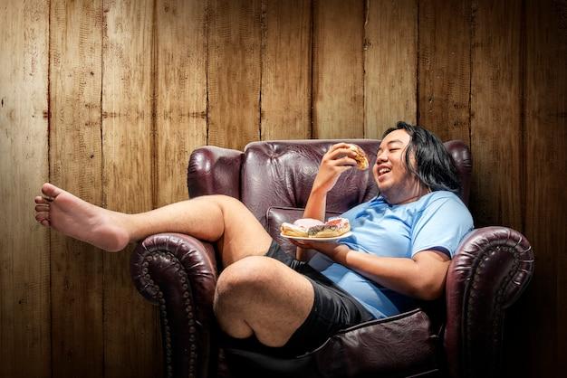 Asiatischer fetter mann, der schaumgummiringe auf platte isst Premium Fotos