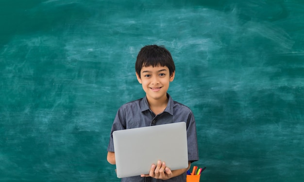 Asiatischer glücklicher schuljunge, der laptop auf schwarzem brett hält Premium Fotos