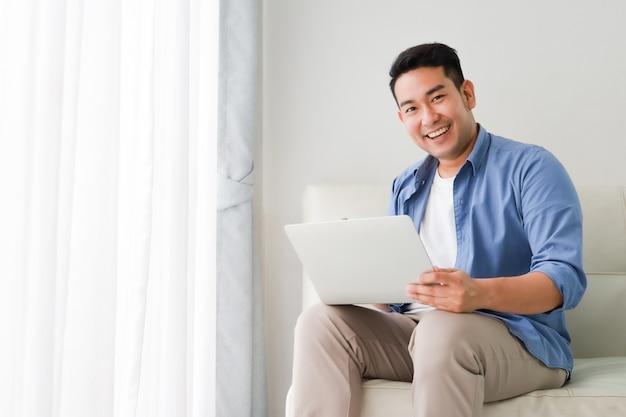 Asiatischer gutaussehender mann, der mit laptop-computer im wohnzimmer glücklich und im lächelngesicht arbeitet Premium Fotos