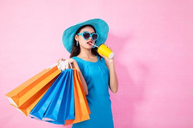 Asiatischer hübscher mädchen sommer, der einkaufstaschen hält, während das wasser und sonnenbrille trinken, die weg auf hintergrund lokalisiert schauen. Premium Fotos