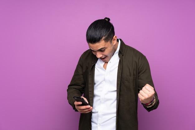 Asiatischer hübscher mann auf blauer wand überrascht und eine nachricht sendend Premium Fotos