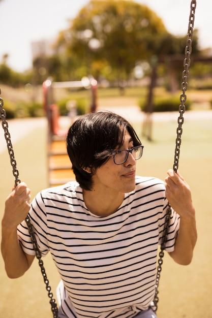 Asiatischer jugendlicher, der auf schwingen sitzt Kostenlose Fotos