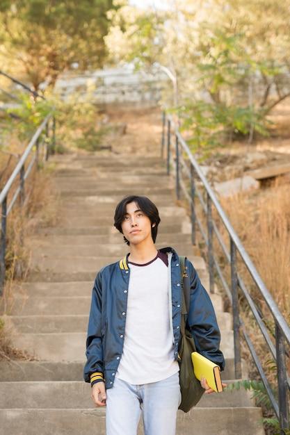Asiatischer jugendlicher, der in der hand treppe mit buch hinuntergeht Kostenlose Fotos