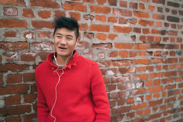 Asiatischer junge, der musik mit kopfhörern hört. Kostenlose Fotos