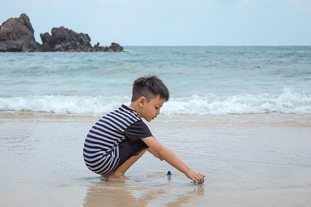 Asiatischer junge, der spielzeug auf einem seestrand spielt. Premium Fotos