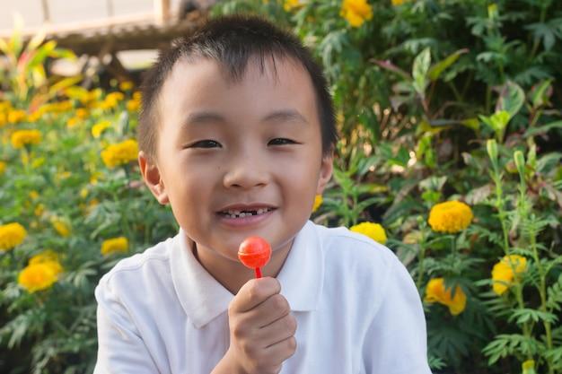 Asiatischer junge, der süßigkeit bis zahnkaries isst Premium Fotos