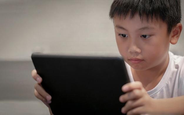 Asiatischer junge, der zu hause spiel auf digitaler tablette, kinder aufpassen karikaturen auf digitalem taplet oder smartphone spielt Premium Fotos