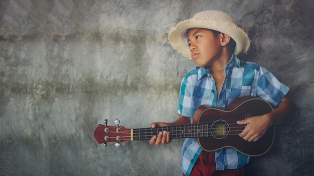 Asiatischer junge im alter von 5-6 spielen ukulele coole geste leidenschaftliche liebe im leeren musikraum Premium Fotos