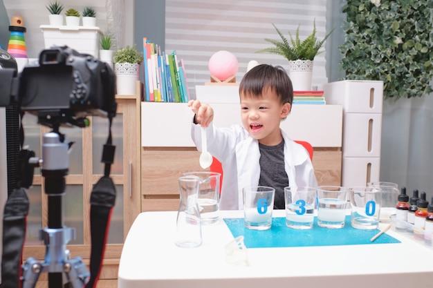 Asiatischer junge macht chemieexperimente und nimmt ein video für seine anhänger auf, junges bloggerkind posiert vor der kamera, kinder machen vlog für social-media-kanal-konzept Premium Fotos