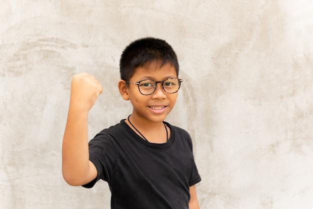 Asiatischer junge mit gläsern reicht oben aus und lächelt über grauem hintergrund. Premium Fotos