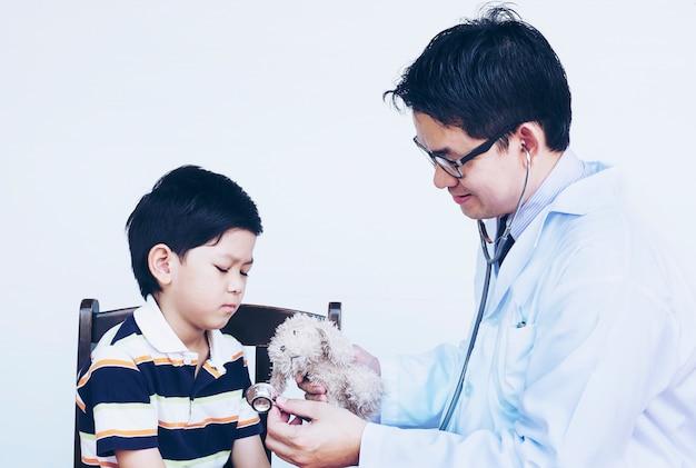 Asiatischer junge und doktor während der prüfung unter verwendung des stethoskops über weißem hintergrund Kostenlose Fotos