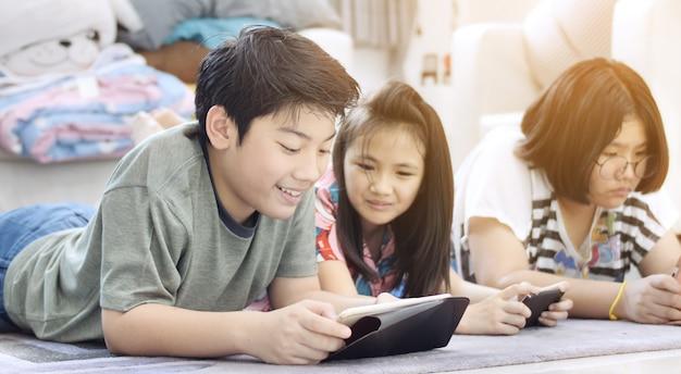 Asiatischer junge und mädchen, die spiel am handy zusammen mit lächelngesicht spielt. Premium Fotos