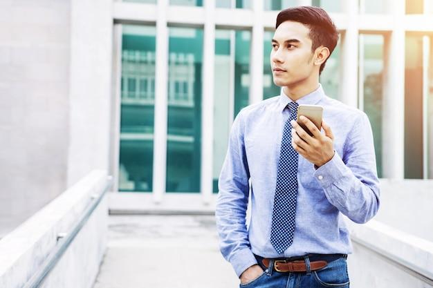 Asiatischer junger geschäftsmann benutzen ein intelligentes telefon und schauen vorwärts Premium Fotos