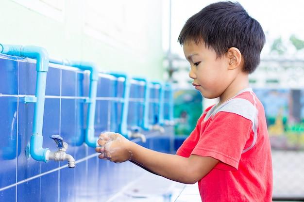 Asiatischer kinderjunge, der seine hände wäscht, bevor lebensmittel gegessen wird. Premium Fotos