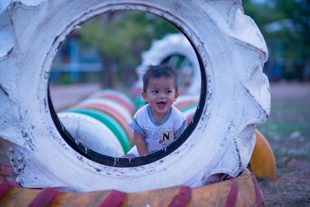 Asiatischer kinderjunge, der spaß hat, auf dem kletternden spielplatz des spielzeugs des kindes in der schule zu spielen Premium Fotos