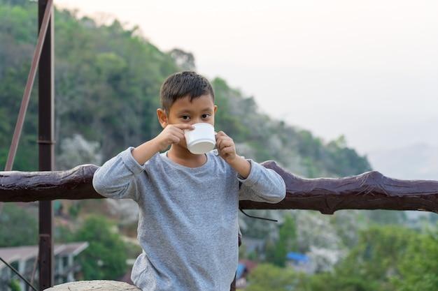 Asiatischer kinderjunge trinkt wasser vom glas. mit blick auf die berge hintergrund Premium Fotos