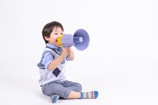 Asiatischer kleiner junge des porträts, der mit glück und freudigem spielen mit megaphon sitzt und lächelt Kostenlose Fotos