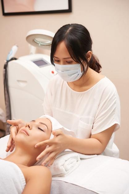 Asiatischer kosmetiker giving caucasian client face massage Kostenlose Fotos